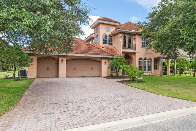 A lovely paver drive and walkway lead up to this stunning custom Kargar pool home, located in the prestigious Woodbridge Estates section of the Plantation Bay golf community,