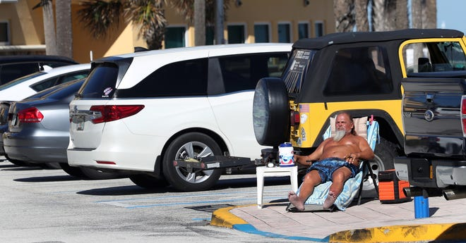 A sunbather catches some rays out of the wind, in the parking lot of Sun Splash Park in Daytona Beach on Tuesday, Nov. 17, 2020.