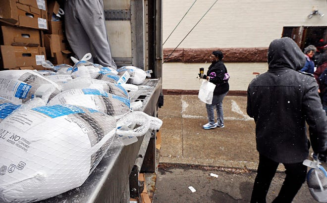 Frozen turkeys, left, are given to people as they exit during the Erie City Mission annual turkey bag distribution in Erie in a previous year.