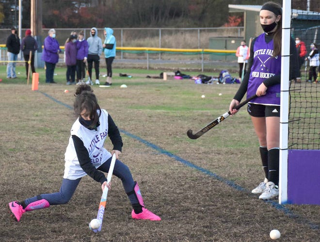 A young player takes a shot with Little Falls varsity Mountie Makena Tooley (right) looking on during drills at the youth field hockey program's Oct. 28 showcase at Veterans Memorial Park.