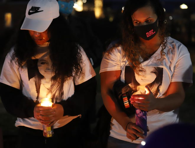 Two women hold candles and wear shirts with the pictureof Riley Degn Smith during a vigil for her Monday night at South Hill Park in Burlington. Smith died of a gunshot wound Nov. 11 in Burlington.