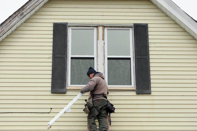 Todd Niles, of West Burlington, owner of Niles Siding and Windows, cuts a piece of aluminum window trim Tuesday while working on a home that is currently being remodeled in Burlington. Niles and his workers were finishing up the job putting the trim on the dozen or so new windows they installed in the home.