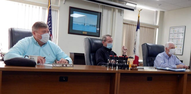 The Des Moines County Board of Supervisors, from left, Bob Beck, chairman, Tom Broeker and Jim Cary, listen to reports during the weekly meeting Tuesday in Burlington. Everyone present wore masks in adherence to Gov. Kim Reynolds' new mandate, which went into effect Tuesday.