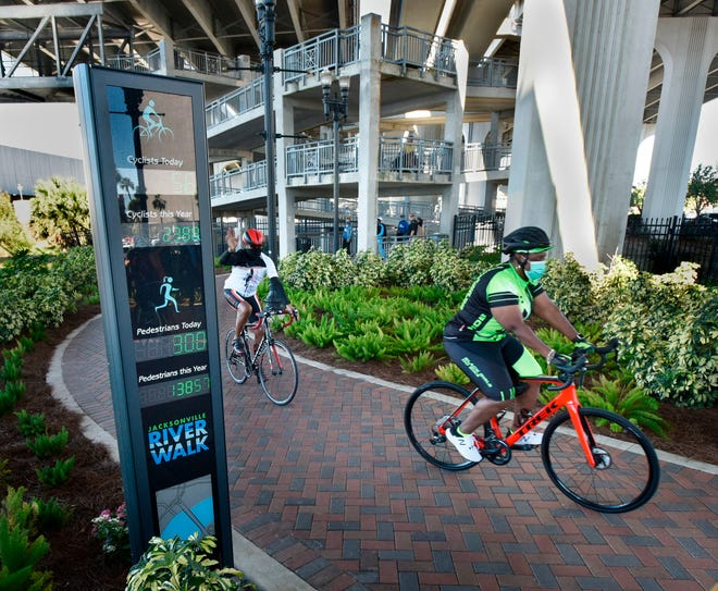 """Bicycles pass by a new """"eco-counter"""" device that counts the number of runners, walkers and bicycles that pass by during a dedication at Corkscrew Park on Jacksonville's Northbank Riverwalk Tuesday."""