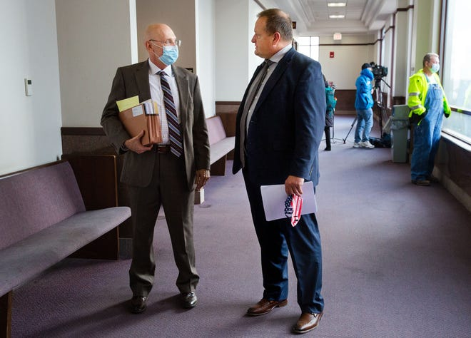 Attorneys John Curley, left, and Thomas DeVore confer in the hallway outside a courtroom in the Sangamon County Building after a judge granted a temporary injunction sought by Sangamon County over four restaurants in Springfield that were continuing to operate without food permits.The restaurants were serving indoor diners Sunday in defiance of the mitigations that went into effect last week and their licenses were suspended. The attorneys represent the restaurants involved. [Ted Schurter/The State Journal-Register]