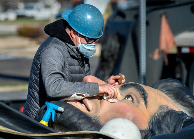 Terry Karpowicz, part of a team of assemblers based in Chicago, cleans up Abraham Lincoln's eyes and face before lifting the 32-foot tall sculpture into place Tuesday near the Washington Fire Station and Five Points Washington in Washington.