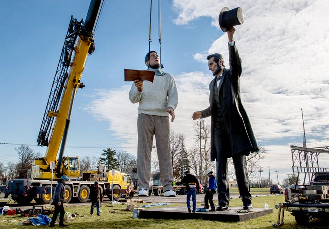 "Workers lower the 26-foot tall ""common man"" section of famed sculptor Seward Johnson's ""Return Visit"" bronze sculpture onto its pedestal Tuesday next to a 32-foot tall, 19-ton version of Abraham Lincoln near the Washington Fire Station on North Wilmor Road in Washington. The sculpture depicts Lincoln handing off the Gettysburg Address to the ""common man."" The giant artwork was moved from the Abraham Lincoln Presidential Library and Museum in Springfield, where it had been on display since 2019 after a two-year stint at the Peoria Riverfront Museum."