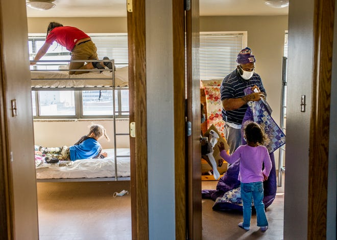 Derek Battles helps his children make up beds in their new home, a three-bedroom apartment at Dream Center Peoria, on Nov. 17. Five months ago, Battles found himself a single parent when his wife left the family.