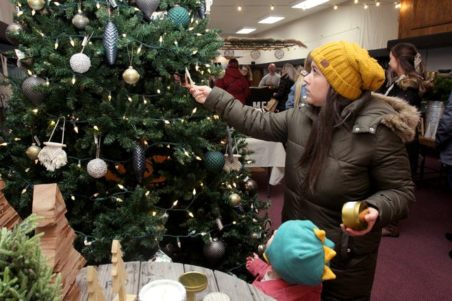 Courtney Buisker, right, of Galena looks at an ornament with her daughter Evelyn at Meier and Co. during the Mistletoe Walk on Sunday, Nov. 24, 2019, in downtown Freeport.