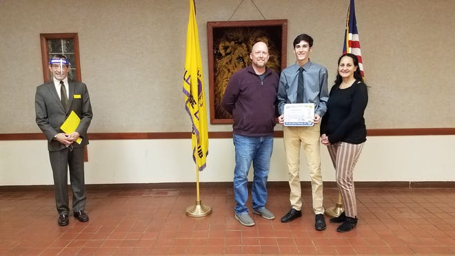 Tallmadge Lions Club member Mark Salerno, left, presents the Tallmadge Lions Club November Jim & Ida Van Glider Student of the Month award to Tallmadge High School student Jacson Queen, along with his parents Jason and Brandy.