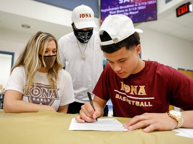 Walter Clayton Jr. signs to play basketball with Iona College on Monday night as his mom Cherie Quarg and dad Walter Clayton Sr. look on at Bartow High School.