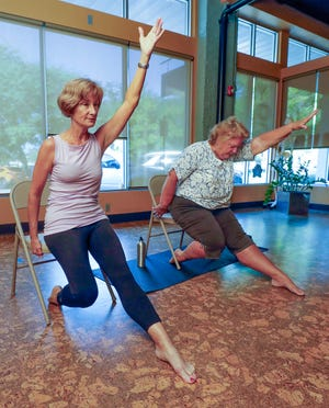 Geri Ross, left, instructor, works with student Linda Collinson during the Chair Yoga class at Inside Out Yoga in Winter Haven.