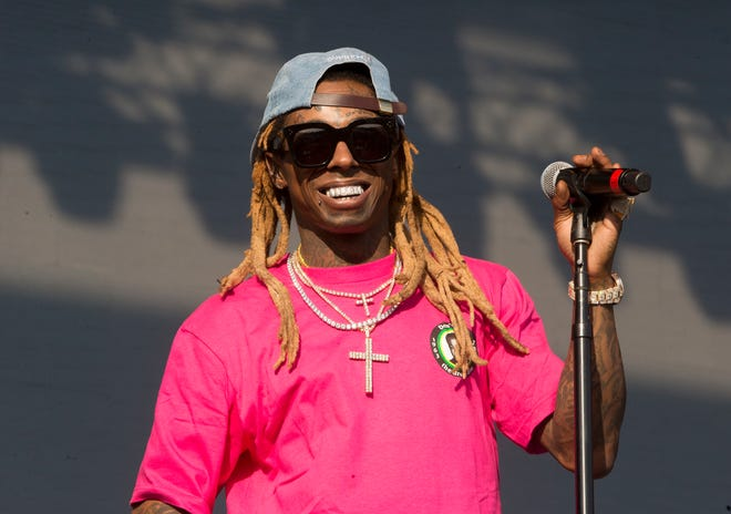 Lil Wayne performs at the Firefly Music Festival in June 2018 at The Woodlands in Dover, Del. The rapper has been charged with possession of a firearm by a convicted felon, an offense that carries a potential sentence of up to 10 years in prison. Documents filed Tuesday in Miami federal court say the rapper, whose real name is Dwayne Michael Carter Jr., had a gun and ammunition on Dec. 23 of last year despite knowing he had the previous felony.