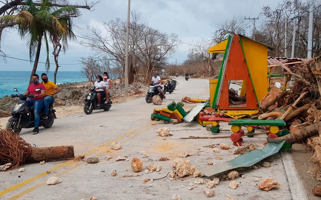 Motorcyclists pass debris on the road after the passing of Hurricane Iota on San Andres Island, Colombia, on Tuesday. Iota moved over the Colombian archipelago of San Andres, Providencia and Santa Catalina, off Nicaragua's coast, as a Category 5 hurricane.