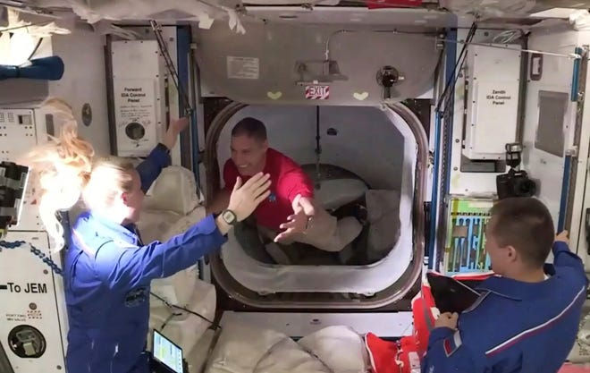 In this frame grab from NASA TV, astronaut Mike Hopkins, center, is greeted by astronaut Kate Rubins, left, as he enters the International Space Station from the vestibule between the SpaceX Dragon capsule and the ISS early Tuesday. At right is Expedition 64 commander Sergey Ryzhikov.