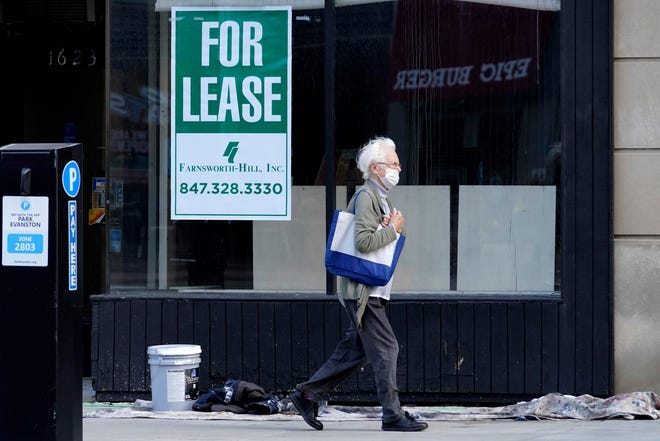 """A man walks past an empty store with a """"For Lease"""" sign in downtown Evanston, Ill., earlier this month. States are renewing their push for more federal money to deal with the fallout from the coronavirus outbreak and to help them distribute a vaccine when one becomes widely available sometime in 2021."""