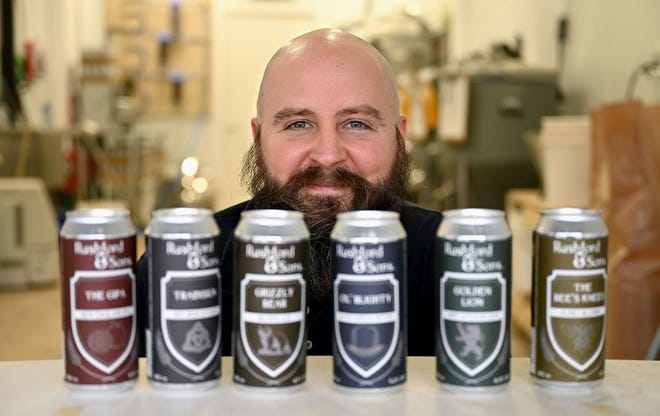 Mike Rushford, head brewer at Rushford & Sons Brewery in Upton, with cans of Rushford & Sons beer. The brewery is opening in the center of Upton next month with curbside pickup.