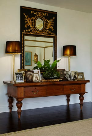 In a show-house room designed by Mimi Masri of MMDesigns, photographs are displayed on a table place beneath a mirror.
