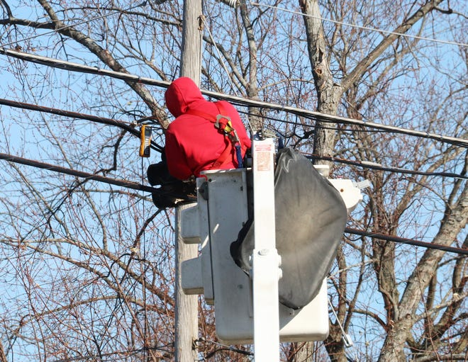 A lineman for Frontier Communications works on wires at a pole across from Pontiac Township High School Tuesday morning.