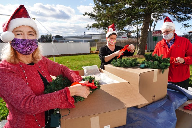 Colleen Westcott, director of Events and Marketing for the Hampton Area Chamber of Commerce, left, assembles a lighted wreath with chamber members Caren MacAskill, Lisa Stonesifer and Dean Merrill, as part of new Hampton Holiday Hunt event.