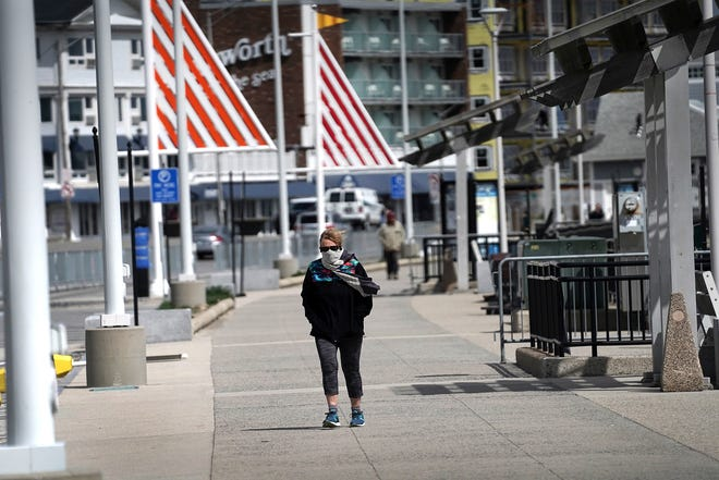 A woman with a face mask and scarf walks along Ocean Boulevard at Hampton Beach on a sunny and windy day in late April.