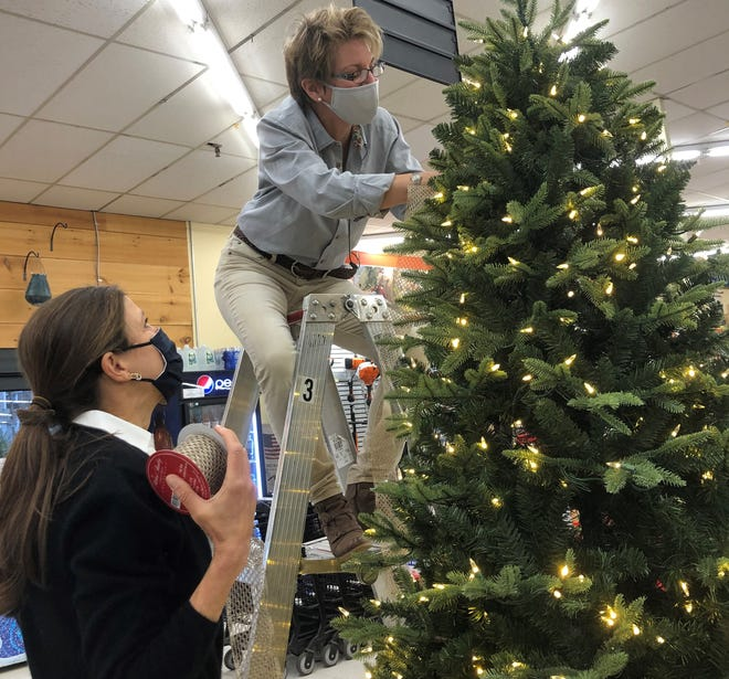 Christine Paccito strings ribbon on one of two raffle trees for this year's Festival of Trees with help from Lisa Lortie.