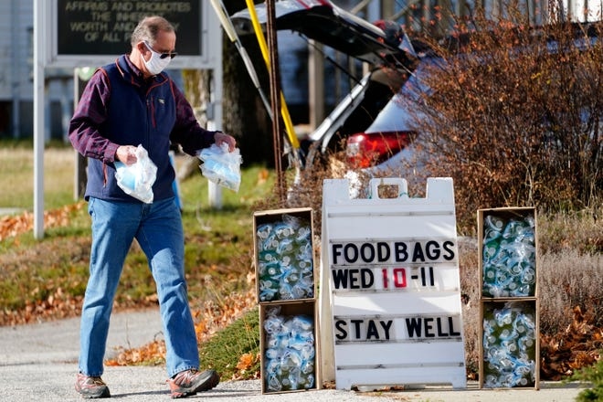 Peter Kaurup wears a face covering to help prevent the spread of the coronavirus, while putting out free hygiene kits outside the First Universalist Church, Monday, Nov. 16, 2020, in Norway, Maine.