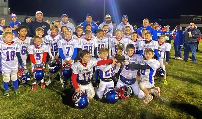 Members of the Winnacunnet Little Warriors youth football team celebrate after beating Merrimack, 22-12 on Saturday in the Northeast Junior High School youth championship at Winnacunnet High School.