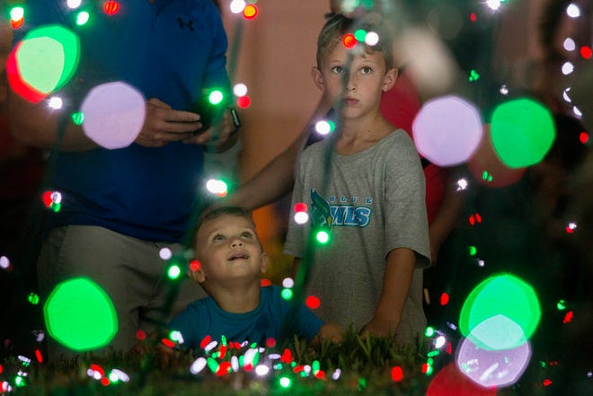 Ethan Foster (right), 8, of Naples, and his cousin Sebastian Wyrick, 3, of Palm Beach Gardens, watch a light show during the holiday tree lighting at Downtown Palm Gardens in this 2018 photo. This year's holiday light show begins Friday.