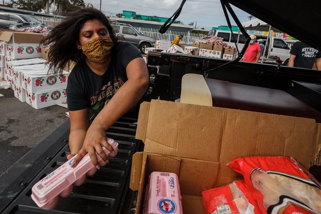 Bunny Rivera of Lantana loads eggs in a truck bed Nov. 17 at the drive-through Feeding South Florida event at the Hatch 1121 Building in Lake Worth Beach. Dozens of cars queued on eastbound Lake Avenue to pick up food.