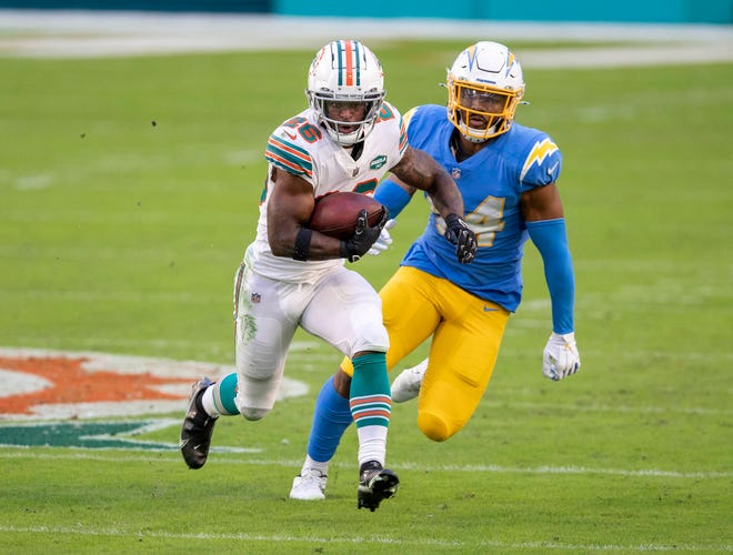 Dolphins running back Salvon Ahmed is chased by Los Angeles Chargers linebacker Kyzir White.