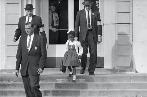 US deputy marshals escort 6-year-old Ruby Bridges outside William Frantz Public School in New Orleans in 1960. [AP Photo]