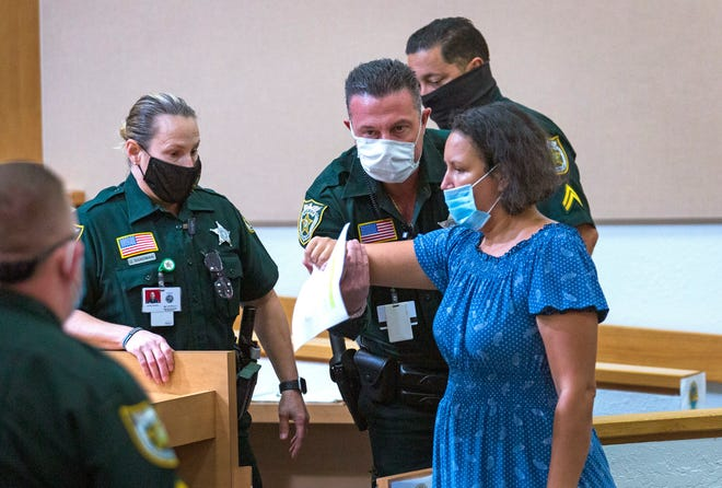 Deputies take Nina Boiton from the Palm Beach Beach County Commission chambers Tuesday after she demanded commissioners do more to control COVID-19, and would not stop speaking after Mayor Dave Kerner told her she had to wait until the proper time for public comments.