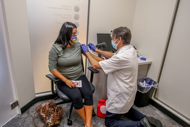 Rhonda McBurney of Providence gets her flu shot from pharmacist Joe Sayles at the CVS on Hope Street in Providence in September. CVS is among the first companies in the United States that will be providing COVID-19 vaccines.
