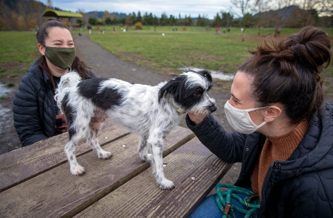 """Addy Hoover, right, pets her dog, Caspian, while at the Amazon Dog Park with friend, Nikki Evans, last week in Eugene. """"You've got to do what you can to protect yourself,"""" said Evans, who is a nurse."""