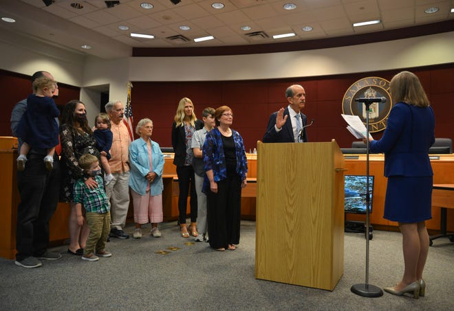 Newly elected District 5 Sarasota County Commissioner Ron Cutsinger is sworn in on Tuesday as his family watches.
