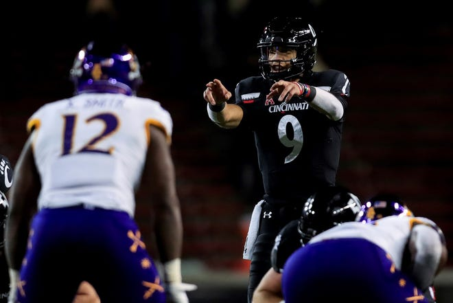 Cincinnati quarterback Desmond Ridder signals to teammates during last week's win against East Carolina. (AP Photo/Aaron Doster)