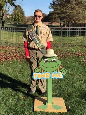 Jackson High School student Ben Weaver with one of his Find Me FeLeap signs he made for a scavenger hunt project for Stark Parks.