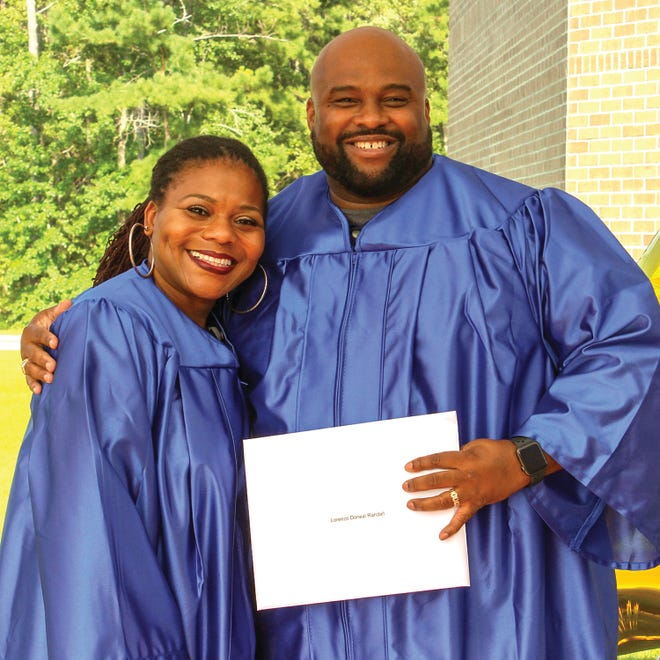 Tracie J. Hardin, left, and Lorenzo D. Randall smile after they receive their Associate in Applied Science degrees in Electroneurodiagnostic Technology at Pamlico Community College's outdoor Commencement ceremony in July. The road to graduation begins with registration, which is underway now. [CONTRIBUTED PHOTO]
