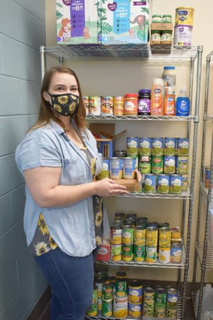 Craven CC student ambassador Leigh Anne Hollar stocks canned goods in the college's Panther Pantry. The Campus Life department is holding a Thanksgiving Meal Drive through Friday, Nov. 20 for students and employees in need during the holidays. [CONTRIBUTED PHOTO]