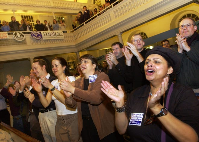 Members of the gay and lesbian community and their supporters stand and applaud during a rally at the Old South Meeting House in Boston, Nov. 18, 2003, after the Massachusetts Supreme Judicial Court ruled that same-sex couples are legally entitled to wed under the state constitution.