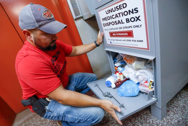 A narcotics detective retrieves unused medications from a police department's disposal box in Barberton, Ohio.