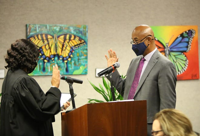 Reelected Alachua County Commissioner Charles Chestnut IV takes the oath of office during a swearing-in ceremony for new commissioners Tuesday.
