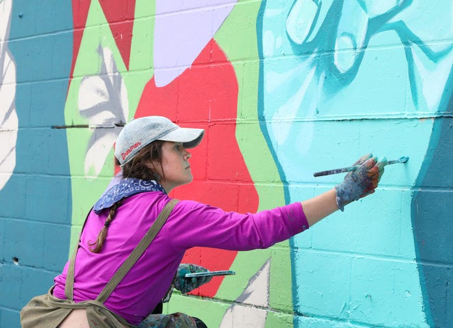Artist Jenna Horner works on a mural that is part of the City of Gainesville's 5th Avenue Wall Project at Springhill on May 19.