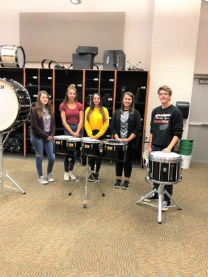 Haylea Hilton (left), Karli Curfman, Leah Fry, Music and Band Director Lacey Kinsey and Luke Burk practice in the  high school band room at Strasburg.