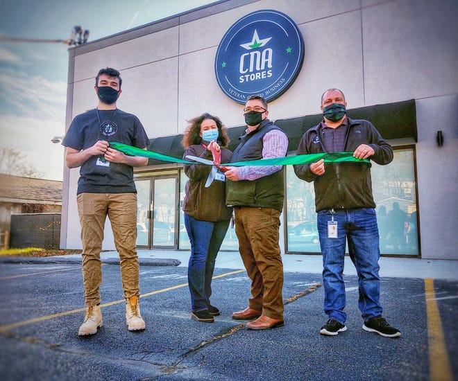 Navy veteran Rob DiFazio, center-right, owner of Amesbury-based recreational-use cannabis company CNA Stores, opened a retail cannabis shop in Haverhill Tuesday. DiFazio is shown here cutting a ceremonial ribbon with his wife, Joy DiFazio, center-left, their son, Niall DiFazio, left, and manager Tom Rossi, right.