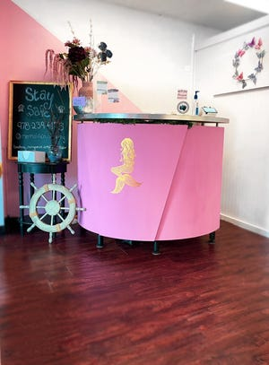 A bright pink desk welcomes clients for their appointments at Mermaid Hair in Beverly Farms.