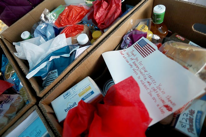 A letter written by a Scituate student is found on the top of a box for a veteran during the Scituate Food Pantry veteran event on Friday, Nov. 13, 2020.