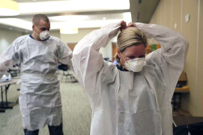 Clinical staff employees dress in personal protective equipment in the Culver Family Welcome Center Tuesday at the University of Wisconsin-Oshkosh to administer COVID-19 testing for the community with 15-minute turnaround time on results.