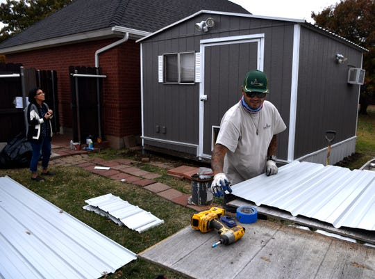 Gus Flores measures a length of tin before cutting it for a skirt for the portable building behind him owned by Melina Sterry (left) on Nov. 13. Flores works for The Honey Do Service of Abilene, a general contractor.